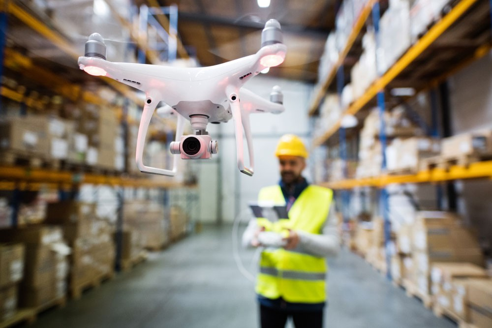 Man operating drone in warehouse.