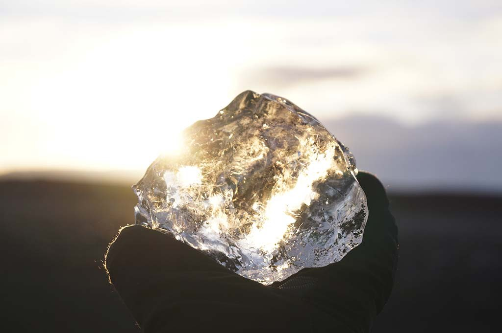 Close-up of a hand holding a diamond in the light