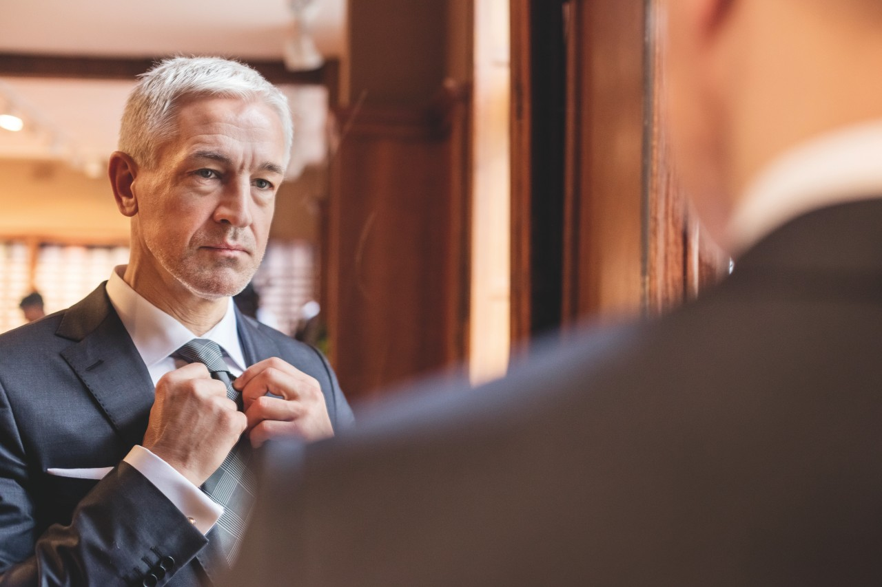 Businessman trying on tie in mirror in menswear shop